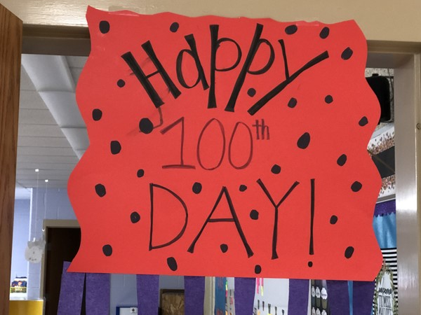Happy 100th Day sign hangs outside Miss Malloy's class.