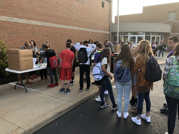 Students waited in line outside of school waiting to receive a binder.