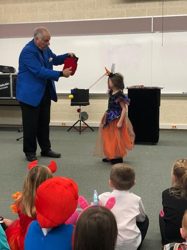 A student performs a magic trick with a magician.