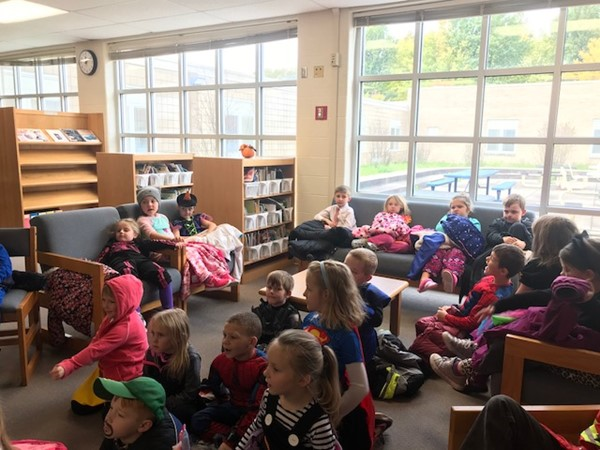 A group of students sit in the library listening to a story