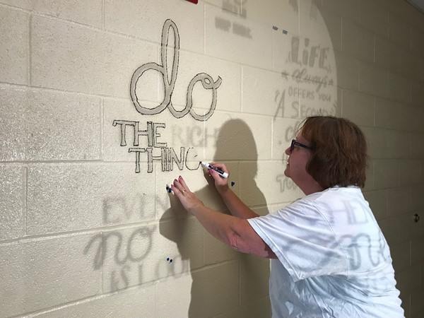 A faculty member draws the cursive lettering outline of Do The Right Thing onto the wall.