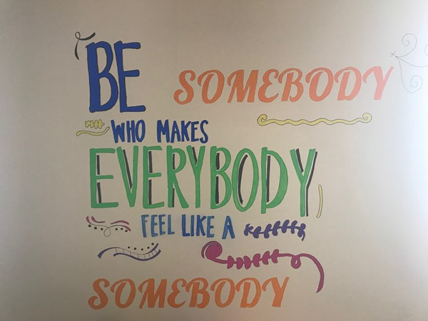 A painting reads Be somebody who makes everybody feel like a somebody.