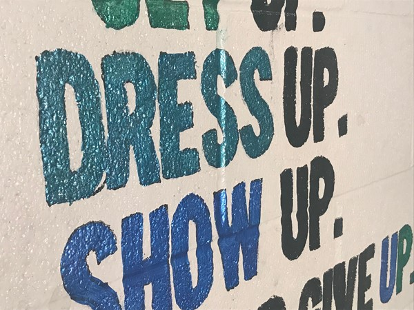 A close up shows green and blue paint inside the words dress and show.