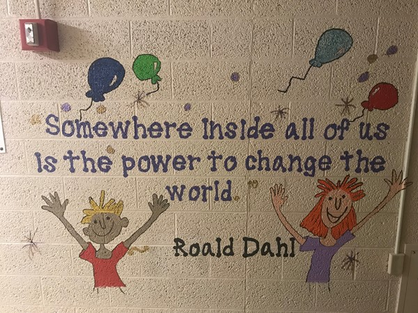 "A Roald Dahl quote is painted on the wall. It says Somewhere inside all of us in the power to change the word."" Painted Balloons and two children are close to the quote."