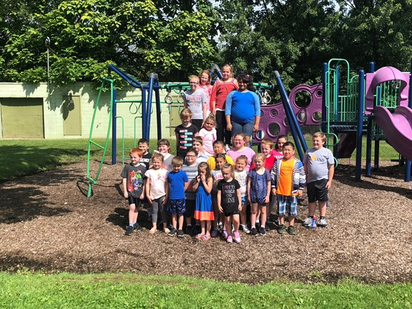 The 24 students that met their summer reading goals pose for a group photo at the park.