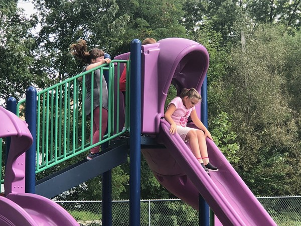 A child is about to slide down a slide at the park.