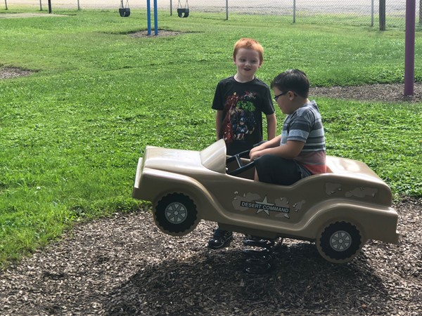 Two children laugh together, while one plays on a car rocker.
