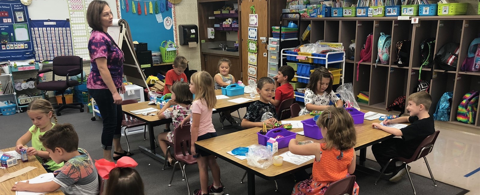 Students in Mrs. Walsh's kindergarten class eat their breakfast and work on a project.
