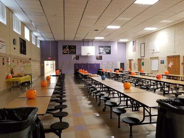 The cafeteria is set up with pumpkins
