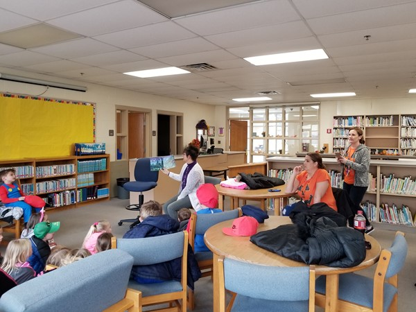 Students sit in the library listening to a Halloween story