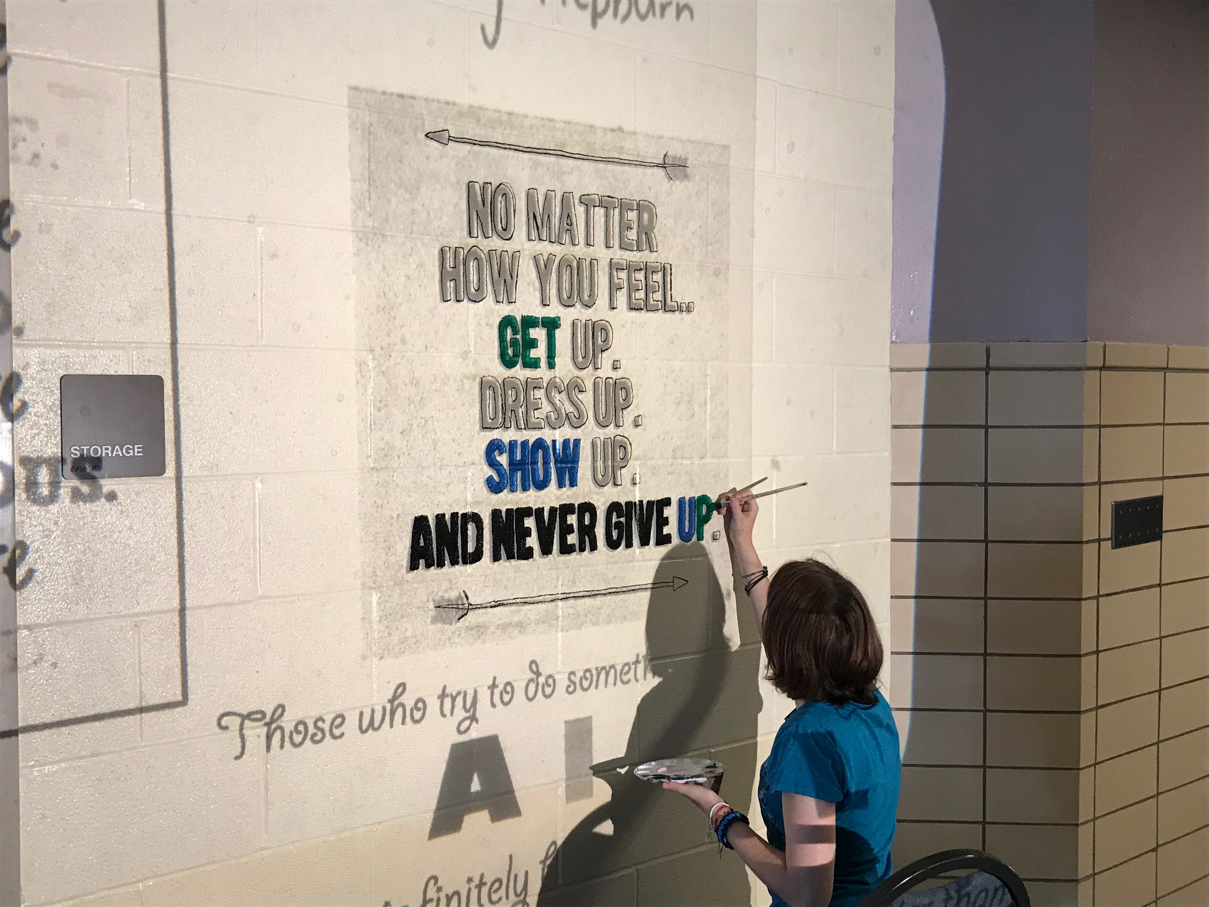A faculty member paints No Matter How You Feel..Get Up. Dress Up. Show Up. And Never Give Up. onto the wall.