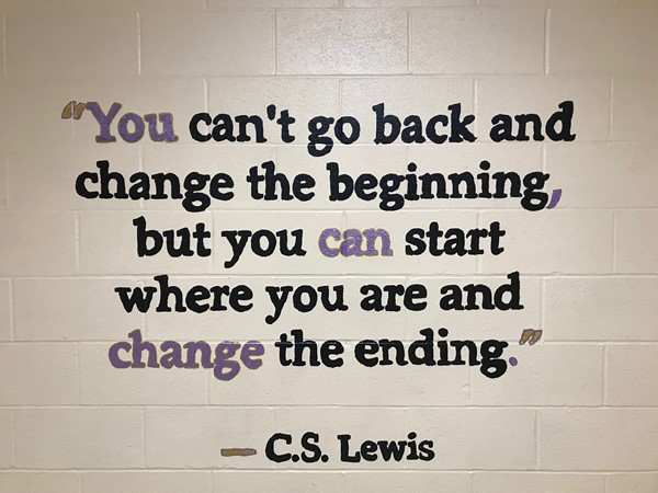 A painted quote reads You can't go back and change the beginning, but yo can start where are and change the ending. by C.S. Lewis.