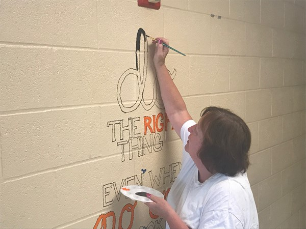 A faculty member fills in a quote with black paint.