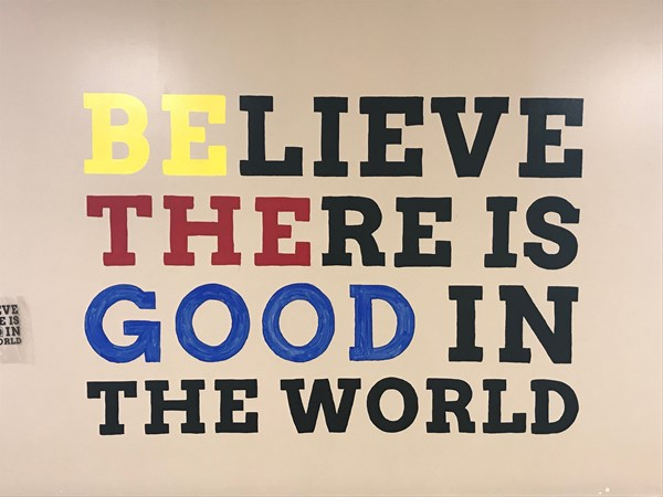 A painting reads Believe there is good in the world. Be the good stands out in a different colored paint.