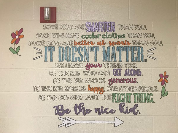 A long message painted on the wall reads Some kids are SMARTER than you. Some kids have cooler clothes than you. Some kids are better at sports than you. IT DOESN'T MATTER. You have your thing too. Be the kid who can get along. Be the kid who is generous. Be the kid who is happy for other people. Be the kid who does the right thing. Be the nice kid.